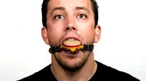Кляп в виде гамбургера во рту у мужчины