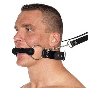 Кляп в виде косточки во рту у мужчины