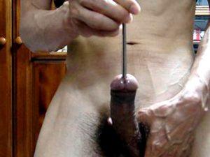 мужчина гей вставляет себе в уретру уретральный расширитель плаг для пениса на стоячем большом члене