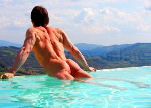 Молодой голый парень с накаченой попой в бассейне