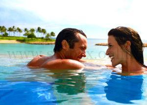 Молодая пара купается в бассейне.
